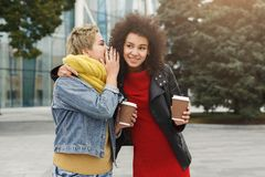 Two female friends sharing secrets outdoors stock photo