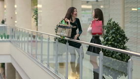 Two female friends with shopping bags in a mall. Two female friends with shopping bags having fun while shopping in a mall stock video
