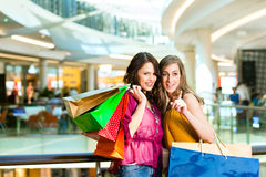 Two female friends shopping in a mall. Two female friends with shopping bags having fun while shopping in a mall Royalty Free Stock Photography