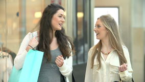Two Female Friends Shopping In Mall Together. Two young women walk through shopping mall carrying bags.Shot on Sony FS700 at frame rate of 25fps stock footage