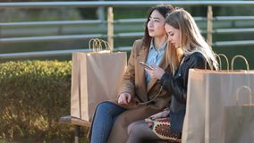 Two female friends shopping online with smartphone stock video footage
