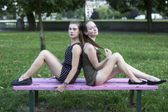 Two female friends sitting back to back on a Park bench. Royalty Free Stock Images