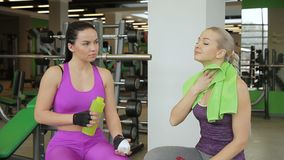 Two female friends are sitting in the gym during the break and talking while resting. Brunette lady in purple sportswear is holding the bottel with water in stock footage