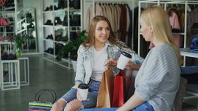Two female friends sitting in large women`s clothing shop and having a conversation after shopping. Modern colourful. Two young female friends sitting in large stock video