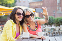 Two female friends sitting and viewing photos on mobile phone Stock Photo