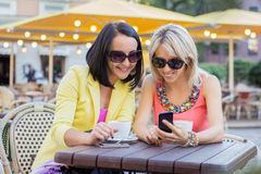 Two female friends sitting and viewing photos on mobile phone Stock Photos