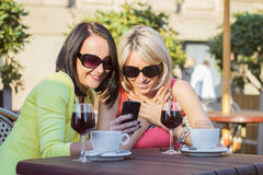 Two female friends sitting and viewing photos on mobile phone Royalty Free Stock Photos
