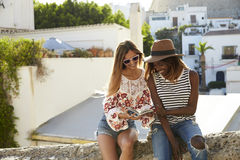 Two female friends sitting on wall reading guidebook, Ibiza Stock Photo