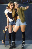 Two female friends at skate park. Hugging friends/ roller blades and skateboard Royalty Free Stock Photo