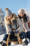 Two female friends sledge downhill in wintertime Stock Images