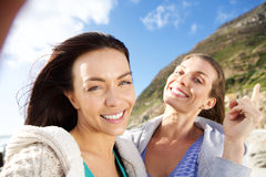 Two female friends smiling and taking selfie. Outdoors Stock Images