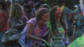 Two female friends spraying colored paint on their friend filming happy moment. Stock footage stock video footage