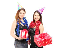 Two female friends standing close together and holding gifts at Stock Images