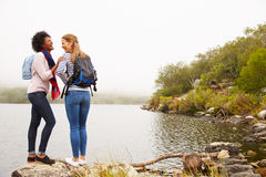 Two female friends standing by the edge of a lake laughing Royalty Free Stock Images