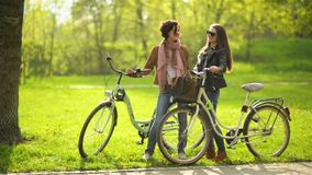 Two Female Friends are Standing in the Park Holding Their Bicycles and Talking to Each Other. Green Grass on Background. Two Female Friends are Standing in the stock footage