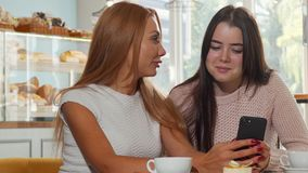 Two female friends surfing internet through smart phone at the coffee shop. Beautiful red haired woman showing something on her phone to her best friend stock video footage