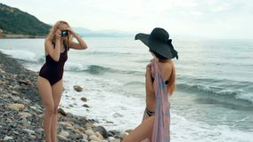 Two female friends in swimsuits taking pictures on camera on beach. Retro concept stock video footage