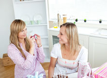 Two female friends taking pictures during a party. Two glowing female friends taking pictures during a birthday party in the kitchen at home Stock Photography