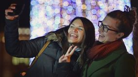Two Female Friends Taking a Selfie Outdoors on Christmas Lights Background. Young Women Photographing Themselves Outside. Using Smartphone. Blurred Xmas Garland stock video