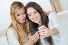 Two female friends taking selfie on sofa. Two female friends taking a selfie on the sofa Royalty Free Stock Photo