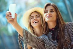 Two female friends taking a selfies, having fun. Outdoor Stock Images