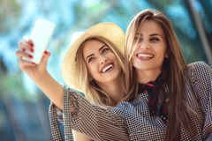 Two female friends taking a selfies. Having fun outdoor Royalty Free Stock Photo