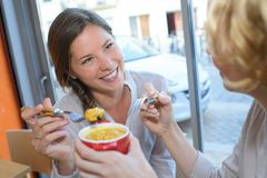 Two female friends talking at cafe table and smiling stock photo