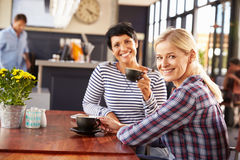 Two female friends talking at a coffee shop Stock Photos