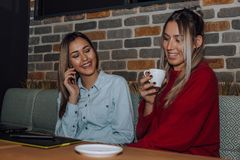 Two female friends talking and drinking coffee in cafe stock image
