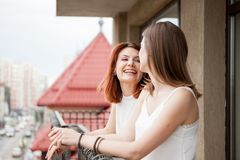 Two female friends talking and laughing at the balcony. The street is visible in the shot Royalty Free Stock Image