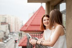 Two female friends talking and laughing at the balcony. The street is visible in the shot Stock Photos