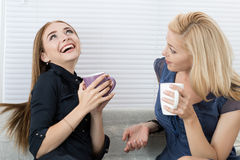 Two female friends talking and laughing together Stock Photo