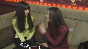 Two female friends talking in a nightclub stock footage