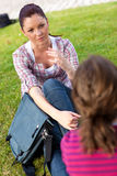 Two female friends talking together on the grass Stock Image