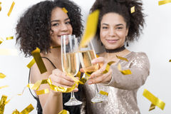 Two female friends toasting with glass of champagne. Under confetti, looking at camera Royalty Free Stock Photo