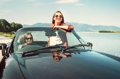 Two female friends travel togehetr by cabriolet car Royalty Free Stock Photos