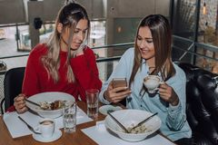Two female friends using a mobile phone during lunch stock photography