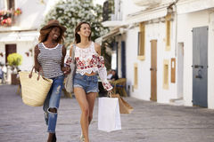 Two female friends on vacation shopping in Ibiza, front view Royalty Free Stock Images