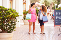 Two Female Friends Walking Along Street With Shopping Bags Stock Photos