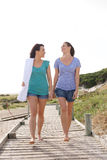Two female friends walking from the beach. Full length portrait of two female friends walking from the beach Stock Image