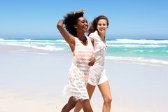 Two female friends walking on beach together Stock Photography