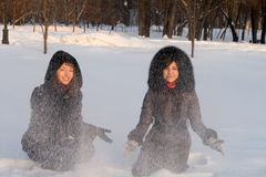 Two female friends walking in park. In winter stock images