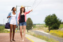 Two female friends walking on railroad station Royalty Free Stock Image