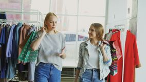 Two female friends are walking slowly through spacious boutique. They are holding numerous paper bags, chatting and. Two female friends are walking slowly stock video footage