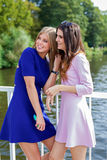 Two female friends watching somebody. Stock Images