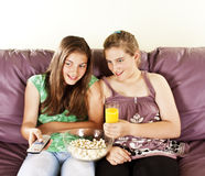 Two female friends watching televison. On the sofa eating popcorn Stock Images