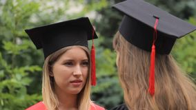 Two female graduates in academic dresses talking after graduation ceremony stock video footage