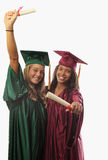 Two female graduates in cap and gown Royalty Free Stock Images