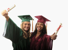 Two female graduates in cap and gown Royalty Free Stock Photo