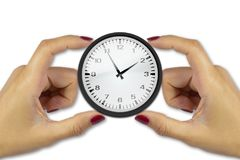 Two female hands holding a clock on white background keep time c Royalty Free Stock Photo
